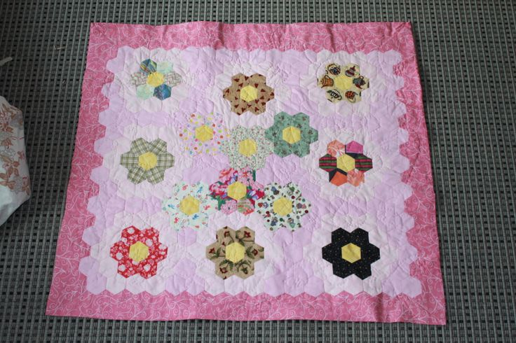 Neas Flowergarden. A baby quilt completely hand sewn. Some of the fabrics used go back to Neas maternal great grandparents and parents wedding quilt.