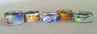 Creazioni e manufatti di Aldina. Serie di anelli in rame smaltati a fuoco e fili di vetro.