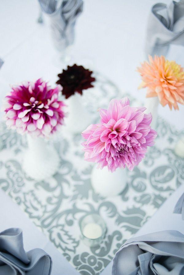 на столе. белые вазы с 1 цветком