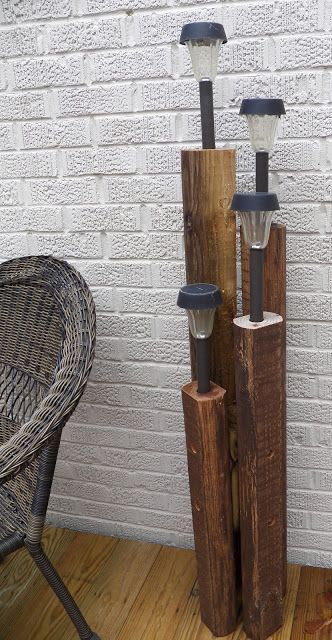 Pier-style posts with inexpensive solar lights. Appears to be 2x4s with bull nose edges, with a dark stain. For stability, they should be tethered together. This would be fun along a walkway with heavy boating rope for a beachy look.
