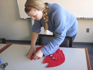 Online editor Laura Lofgren makes claws for the lobster costume by cutting red felt and using a hot glue gun to attach the material to red gloves.