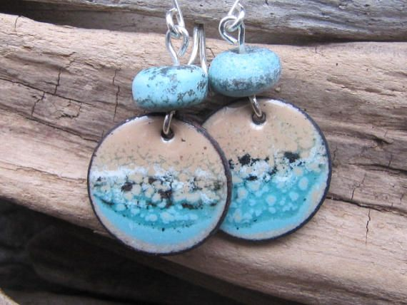 A wearable piece of art...handmade watercolor 3/4 inch disk earrings created with a layered effect of glass enamel in hues of aqua blue and sand. Finished with simple handmade sterling silver wires and handcrafted lampwork beads. One of a kind inspirations from the Pacific Ocean; crashing waves, a day at the beach. Approximate Size: 1 3/4 inches long from top of wire to bottom of the charm. The importance of counter enameling (typically a solid dark color on the backside) is pivota...