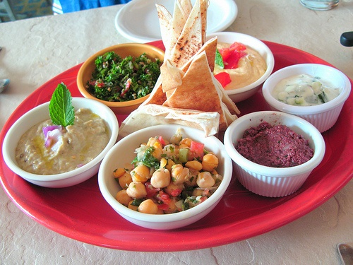 Mezze Platter - pita chips with dips like tzatziki, hummous, baba ghannouj, roasted garlic & pepper& salads like tabouli, chickpea salad or cucumber salad, can include olives or cheeses.  A lot of this is easy to get premade. (credit:Cape Cod by jasonperlow, via Flickr)
