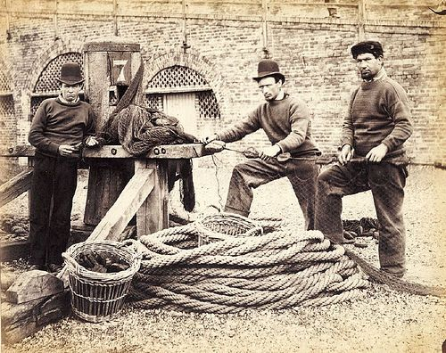 Monochrome print of three fishermen standing by a capstan on Brighton beach. The man on the left of the camera holds a knife and a section of netting. The two men on the right hold a rope that is fixed to the capstan. 1860s