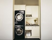 Laundry Room. Stacking washer and dryer with a cabinet above.