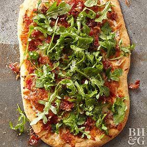 The flatbread recipe is full of Mediterranean flavor thanks to tomato pesto, prosciutto, provolone cheese, and peppery arugula.