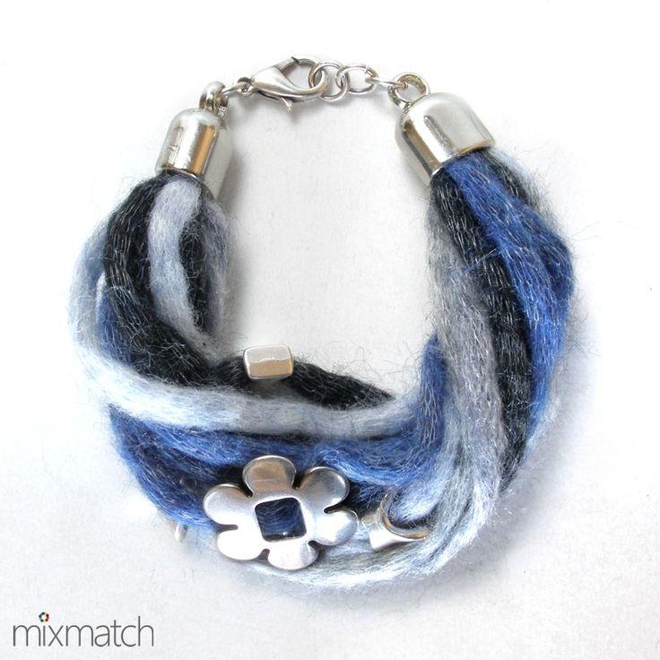 Βραχιόλι από ακρυλικό νήμα σε μπλε και γκρι αποχρώσεις με μεταλλικό λουλούδι και ακρυλικά επιμεταλλωμένα στοιχεία σε ασημένιο χρώμα.