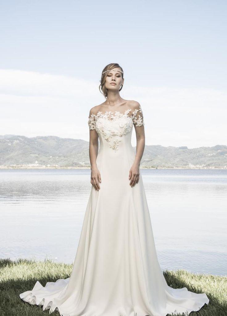 Abito da sposa   realizzato in morbido satin color bianco seta   rifinito da fiori rosa pallido in rilievo sul decoltè