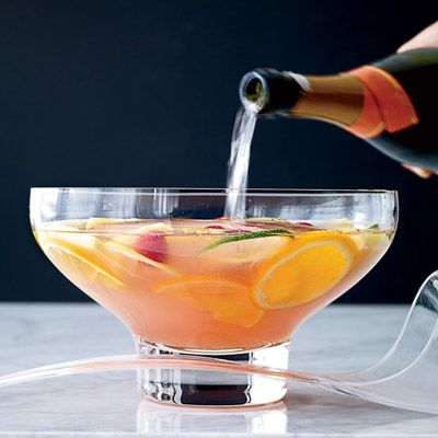 Holiday Punch Recipes2 oranges, thinly sliced 2 lemons, thinly sliced 1 lime, thinly sliced 1/2 pint(s) raspberries 1 cup(s) fresh pineapple, cubed 1 bottle(s) Dorothy Parker gin 1 3/4 cup(s) lemon juice, freshly squeezed 1 1/4 cup(s) simple syrup 1/2 cup(s) orgeat syrup 1 cup(s) framboise liqueur 1 bottle(s) Prosecco, chilled 1 block of ice