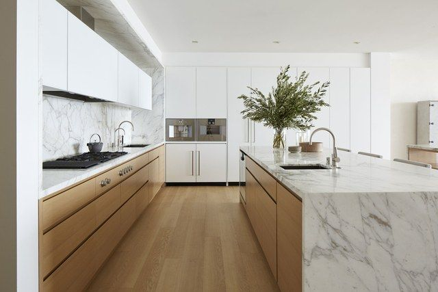 """Two dishwashers, two fridges (one for wine, one for everything else), and a pantry space are all concealed within the kitchen's polished custom cabinetry. An inset espresso machine—admittedly the client's most-used appliance—keeps the marble-topped island and countertops clear of clutter. """"It's become totally indispensable. We have a bunch of caffeine addicts in the family,"""" says the husband."""