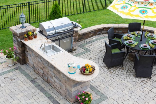 This is such an adorable outdoor kitchen patio design idea. Everything about it just looks cute, comfortable and playful. Mixing intricate brick work with playful pops of color like the color featured on the patio chairs and placemats is a fun way to mix up a design. You could use your favorite color and make a scene like this truly unique and exactly to your specifications. It'd be the perfect place for late morning weekend breakfasts.