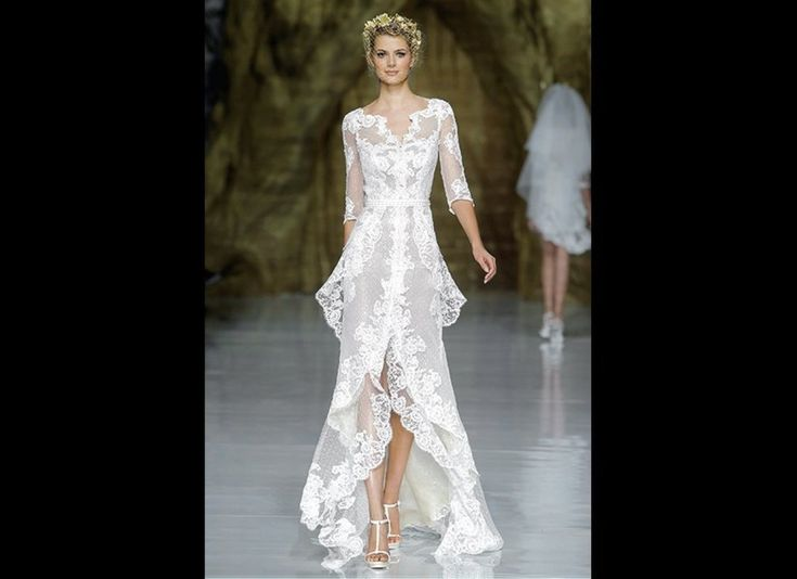 With flattering three-quarter-length sleeves and a fashionable high-low hem, this flowy lace gown by Pronovias was a standout on the bridal runways. - This dress is unbelievably flawless.