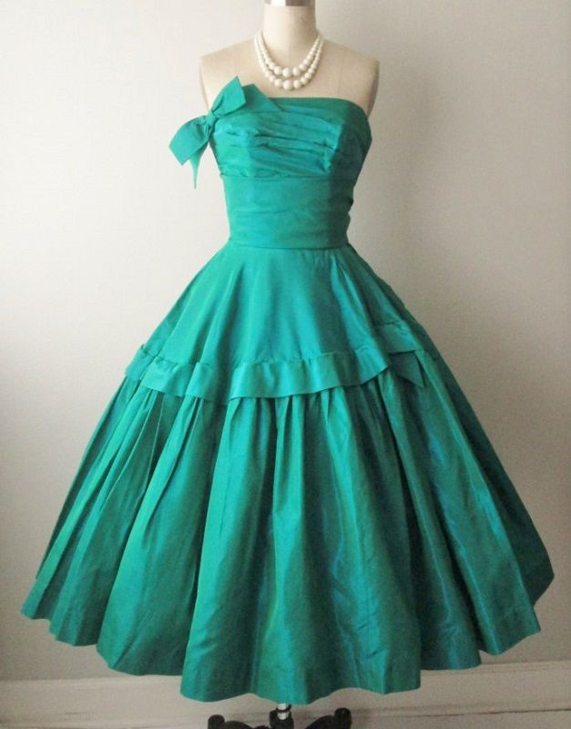 1950's classic silhouette cocktail party dress in brilliant jade taffeta. It features a strapless bodice made with a pleated overlay and bow accent, and dramatic full circle skirt. Dance Originals by Fred Perlberg.