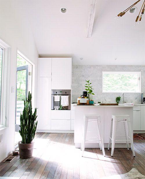Cuisine blanche avec parquet en bois, ouverte sur la terrasse. Le bon plan pour l'été !