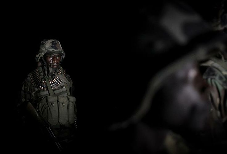 Ugandan troops serving with the African Union Mission in Somalia (AMISOM) form-up in the middle of the night 26 November 2012 ahead of a ground advance as part of a joint Somali National Army (SNA) and AMISOM operation in an area south-west of the Somali capital Mogadishu.