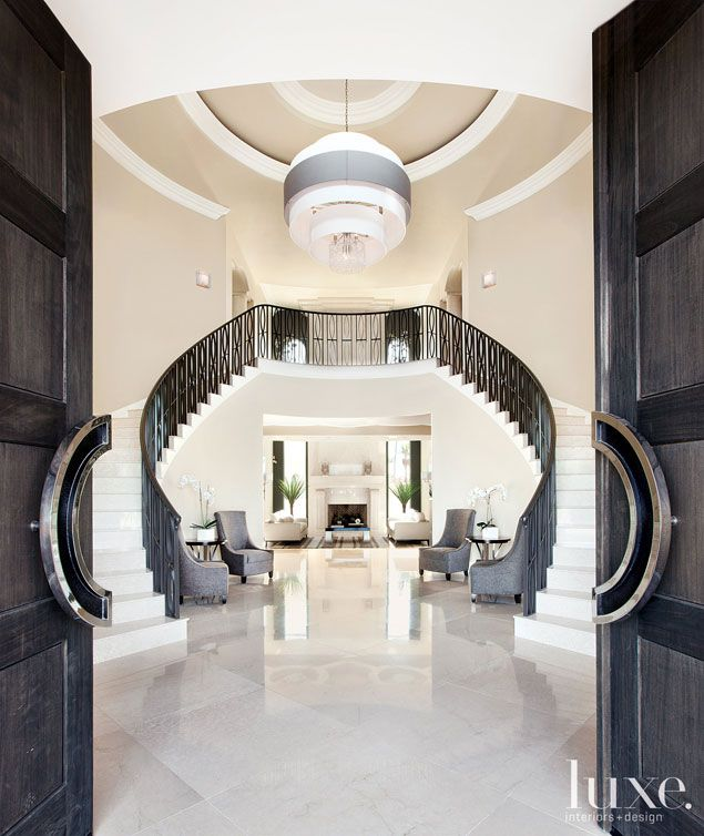 This sleek and shiny entrance opens up to a 24-foot-high foyer, and a modern palette of neutral hues and textured materials.