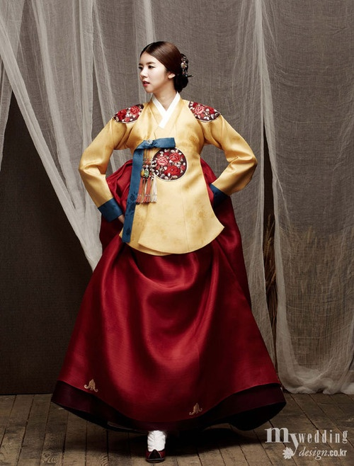 Gold jacket with white under-portion. Blue sleeve extended to large sleeve ended in small edge of white. Cerulean blue sash. Red top skirt fabric, white bottom skirt fabric. Male color be predominantly blue and gold with red and white hints.