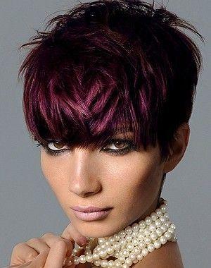 Capelli corti con frangia generosa appoggiata sulla fronte, di un color misto tra viola luminoso e rosso mogano.