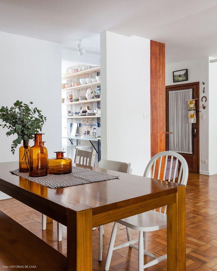 Mesa de madeira, cadeiras brancas com modelos diferentes e garrafas de vidro usadas como vasos.