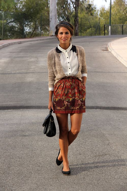 White Button Up under an earth-toned Cardigan worn with a dark print Skirt; black accents.