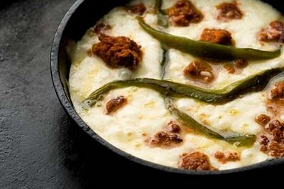 "QUESO FLAMEADO aka QUESO FUNDIDO  ~~~ queso flameado is, traditionally, a dish of hot melted cheese and spicy mexican chorizo (often served flambe).  this dish is popular in north mexico and on tex-mex cuisine menus. recipe gateway: this post's link AND a share from the book, ""mexian everyday""  by rick bayless that incorporates tequila minus the chorizo at http://www.foodandwine.com/recipes/baylesss-queso-fundido-al-tequila [Mexico] [homesicktexan] [Rick Bayless] [foodandwine]"