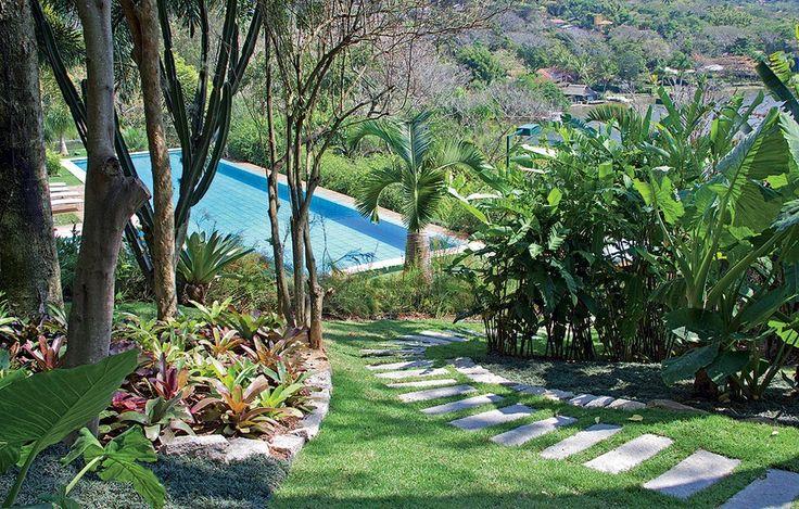 O azul da piscina contrasta na imensidão verde das bananeiras, moreias, palmeiras-garrafa, bromélias e palmeiras-rabo-de-raposa. É de espantar qualquer baixo astral! Projeto do paisagista Gilberto Elkis