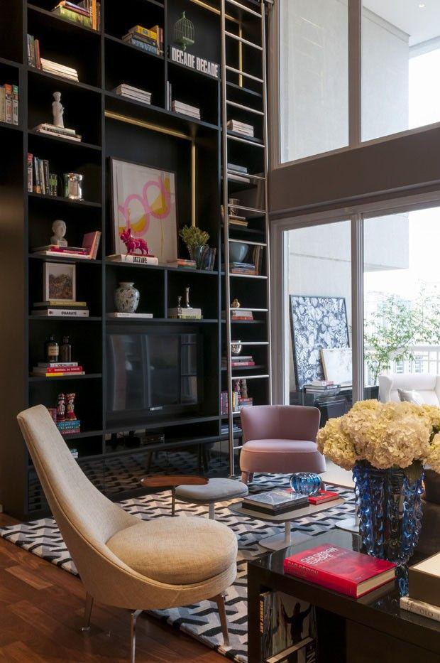 Biblioteca, sala de estar e home theater dividem espaço harmoniosamente. Uma boa dica é misturar, nas prateleiras, livros e objetos decorativos