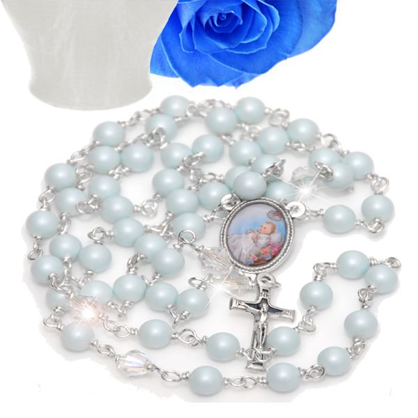 Baby Blue Christening Rosary - A classically beautiful pearl and crystal Christening rosary.  Aves of lustrous 6mm pastel blue Swarovski pearl and Paters of sparkling 6mm clear crystal. The center medal is a silver tone 18mm by 14mm colour depiction of a little boy at his Christening. The crucifix is a beautiful enamelled silver tone design measuring 23mm by 12mm.