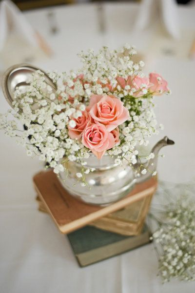 coral roses & baby's breath in a teapot. just add books.