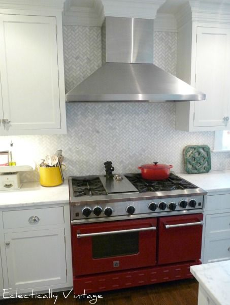 Stunning kitchen renovation - high end details like this red stove, herringbone backsplash to the ceiling, marble counter and more eclecticallyvintage.com