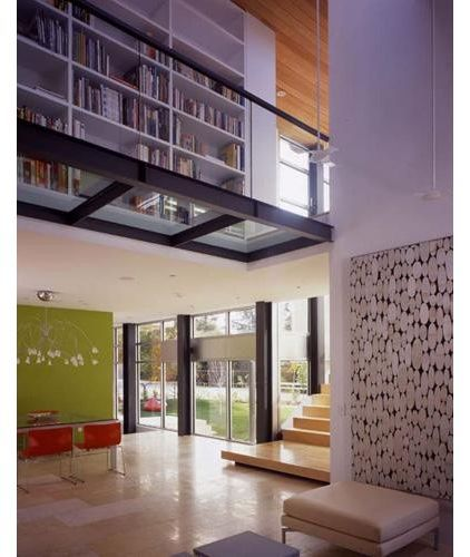 This last batch of examples are technically mezzanines, rather than bridges, but in being open on one side and acting as corridors they are very bridge-like. And elements like the glass floor which is different than the adjacent floor, make this walkway next to a wall of books special.