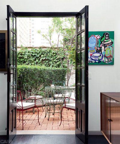 Cadeiras vermelhas, originais de um clube de Santos, SP, vieram de um antiquário e ajudam a conferir uma atmosfera francesa ao jardim. As portas, pintadas de preto, se abrem para uma antessala da suíte principal.