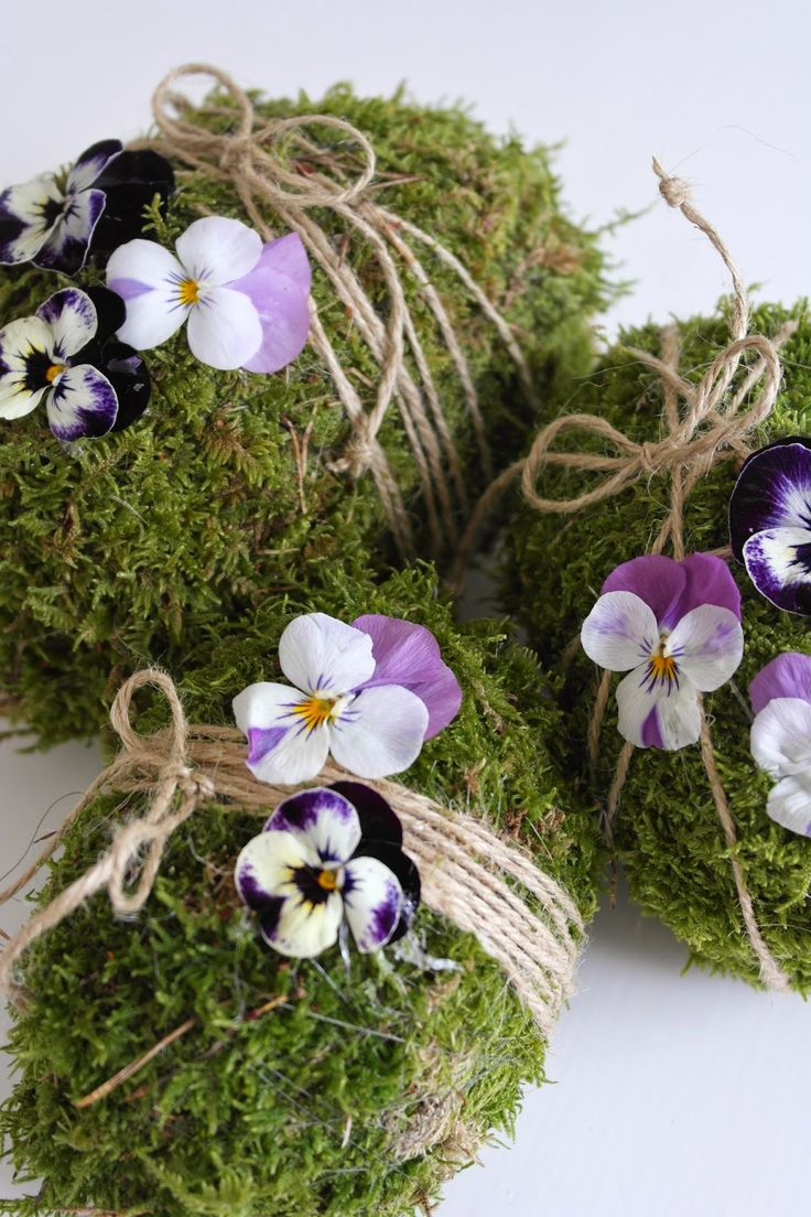 Moss covered eggs wrapped with a couple loops of twine, that are topped with a couple violet blooms