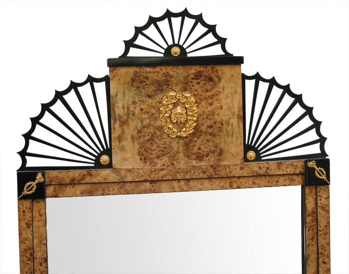 BIEDERMEIER Uniquely designed Russian neo-classical pier-mirror. Veneered with one of the most outstanding and exciting woods: Karelian birch on pine. Stepped frame with ebonized corner-plates and inlaid hairlines. Top with 3 ebonized radial grill-works following the umbrella motif. Original mounts with garlands, feathers, torches, laurel leaves and rosettes. Baltic (Russia), before 1825.