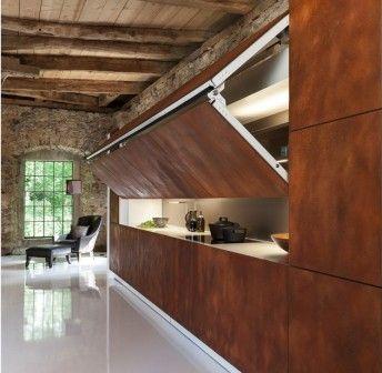 Zupełnie nietypowa lecz designerska aranżacja kuchni. Idealne rozwiązanie do nowoczesnych loftów lub otwartych przestrzeni w domach. Ruchoma ściana odsłania lub przesłania genialnie wyposażoną kuchnię. Jednym ruchem poprzez wciśniecie przycisku siedmiometrowy panel ścienny znika lub pojawia się, tworząc ścianę doskonale zakomponowaną z resztą wnętrza. W ten sposób zapachy z kuchni zostają za ścianą. http://sztuka-wnetrza.pl/1931/artykul/znikajaca-kuchnia