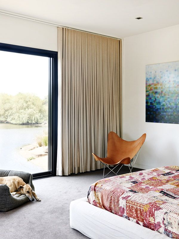 Master bedroom looking out to lake.  Butterfly chair in tan leather, Matthew Johnson artwork, Charlie the greyhound in basket!  Production –...
