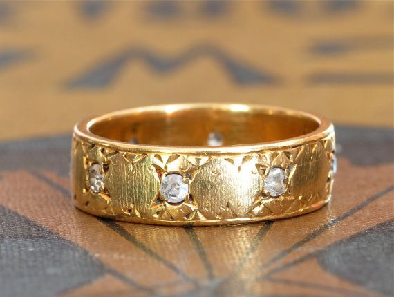 This elegant and substantial 18k yellow gold band features eight .01 carat diamonds bead set into a heavy gold Italian band with hand worked