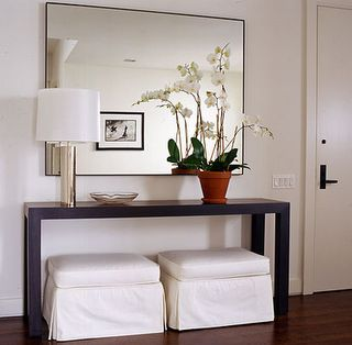 Slipcovered white ottomans and modern wood console table with chrome lamp and large wall mirror! White paint wall color in entry foyer entrance! White brown silver colors in entry entrance foyer.