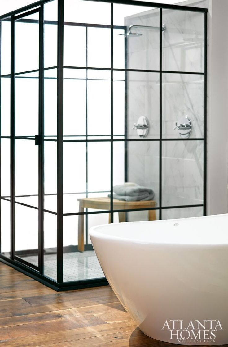 """Modeled after vintage factory windows, the shower's glass-and-aluminum enclosure was fabricated by Atlanta Glass & Mirror, Inc. """"The custom shower came to life from a sketch drawn on an iPad,"""" says designer Dylan Gilliam of Home ReBuilders. """"What makes this bath truly remarkable is that there are so few items straight from stock."""""""