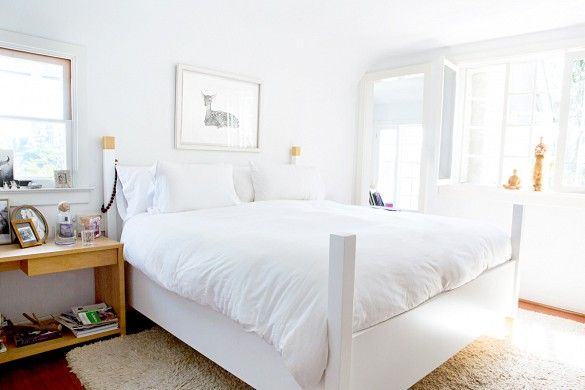 Serene white bedroom space with styled nightstands and framed fawn artwork above bed.