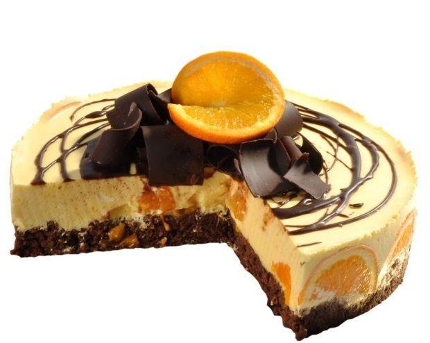Pomerančový dort Originální ovocný dort se základnou z čokoládových corn-lupínků pokrytý lehkým tvarohovým krémem s kousky pomeranče a likérem. Povrch je zdoben plátky pomerančů a čoko hoblinkami.