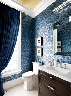 Gorgeous bathroom features walls clad in silver and blue damask wallpaper, Graham & Brown Desire Wallpaper lined with a brown dresser like washstand and a beveled mirror illuminated by a linear wall light across from a window dressed in blue velvet curtains.