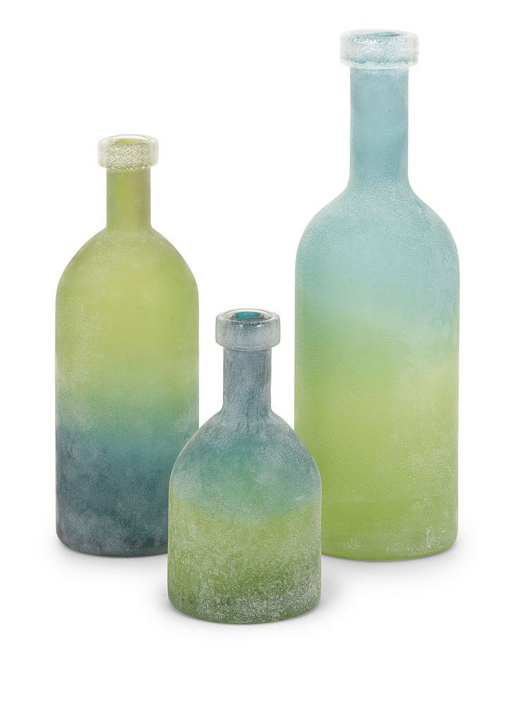 Like tumbled and weathered sea glass, this trio of glass bottles in soothing shades of blue and green appear frosted by sea and sand.