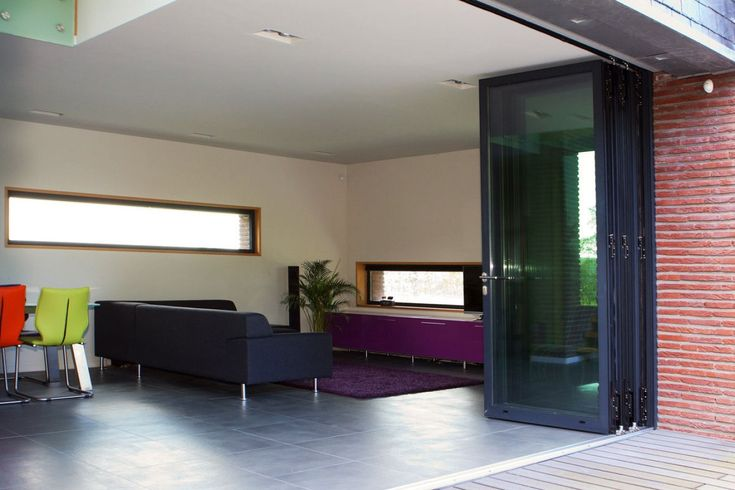 De aluminium vouwdeuren van Reynaers kun je helemaal naar binnen vouwen waardoor de woonkamer geheel naadloos overgaat in het terras.