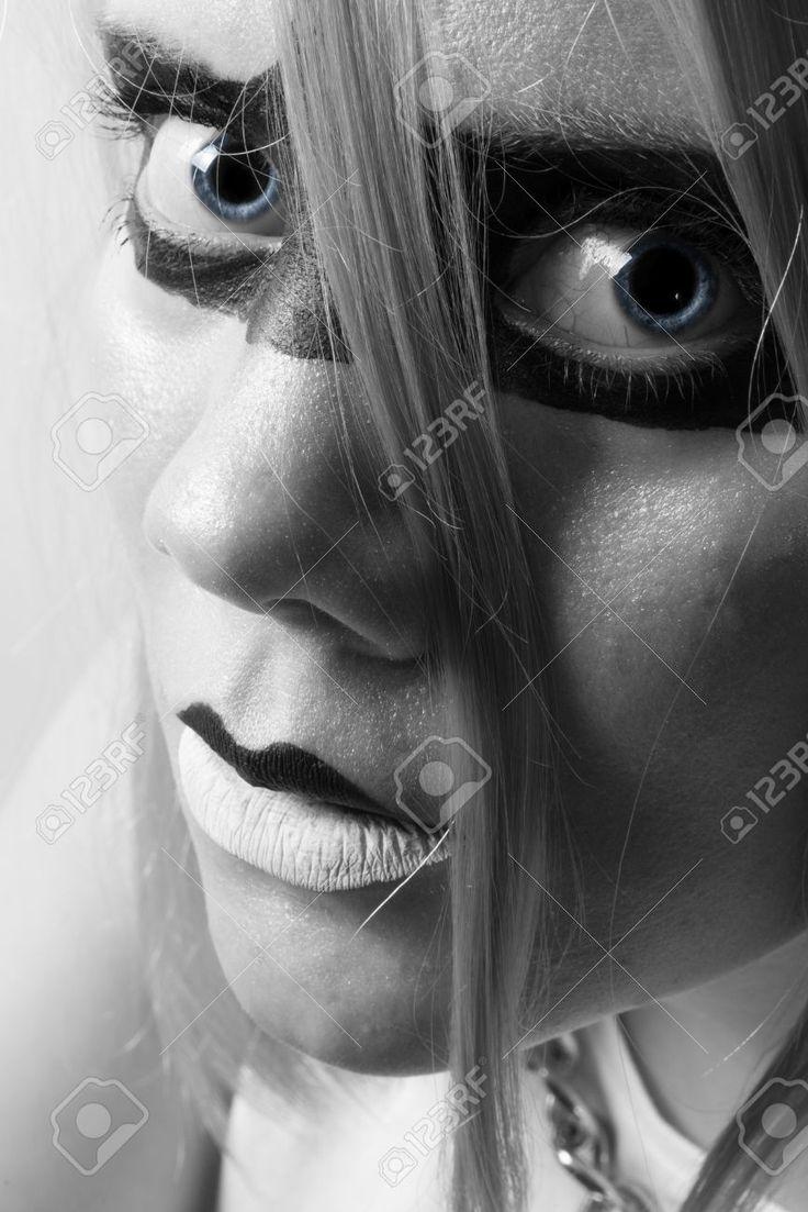 Mujer Joven En Semi Perfil Con Los Ojos Azules Y Maquillaje Negro Alrededor De Los Ojos Mirando Directamente A La Cámara Fotos, Retratos, Imágenes Y Fotografía De Archivo Libres De Derecho. Pic 22853213.