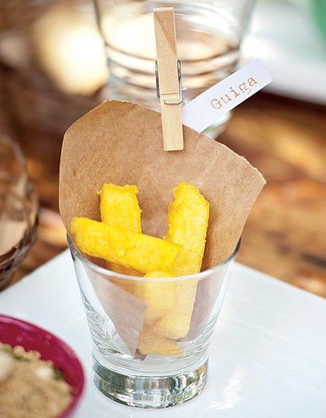 """Com papel kraft dentro, o copo abriga polenta frita. Cada """"kit churrasco"""" exibe o nome de um convidado"""