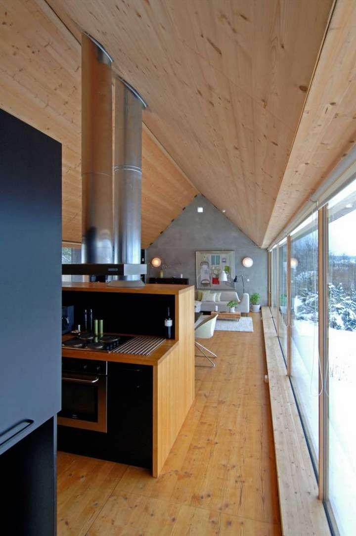 Stuerommet med kjøkkenet i forkant. Til venstre ser vi en snipp av den svartmalte skapet og skilleveggen med garderobe på den ene siden og kjøkkenskap på den andre, som også inneholder deler av husets luft-til-luft-varmepumpeanlegg.