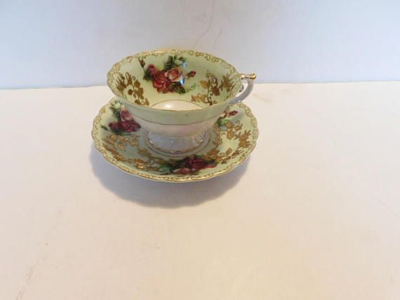 """Handpainted cup and saucer in a red and pinkrose design with a gold vine on a green band, gold accenting  The cup is 2 5/16"""" (5.9 cm) high x 3 7/8"""" (9.8 cm) at the brim and the saucer is 5 7/16"""" (13.8 cm) in diameter  This set is in very good condition and only appears to have seen use as a collectible  Made of chinafrom Occupied Japan by Shafford    These items have no nicks, chips, cracks, or signs of repair 