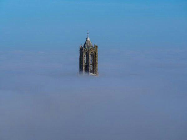 Dom torent net boven de mist uit