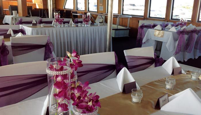 Purple and gold themed table settings on board Showboat Cruises